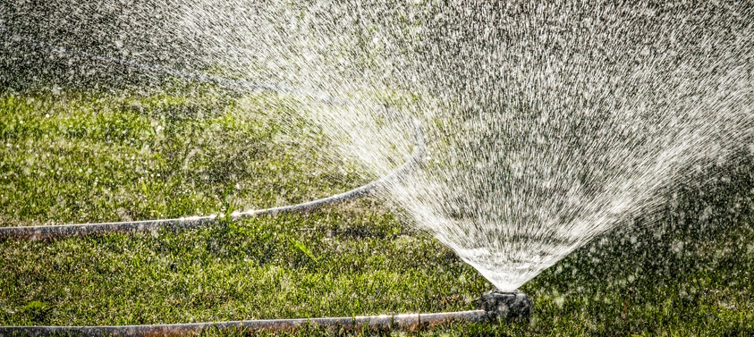 Watering the lawn of a private house with the help of irrigation sprinkler