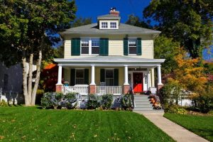 Yellow house dark green lawn fall leaves halloween decorations
